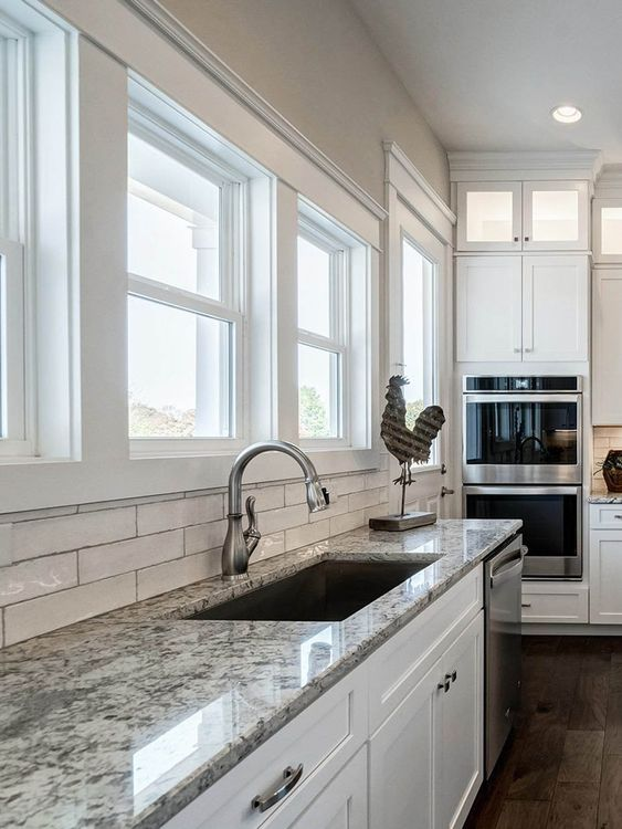 a pretty white kitchen with a white skinny tile backsplash and grey granite countertops plus stainless steel fixtures