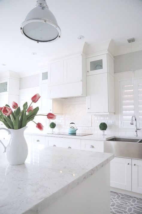 a pure white kitchen with a white tile backsplash and quartz countertops, pendant lamps and metal sinks is very beautiful