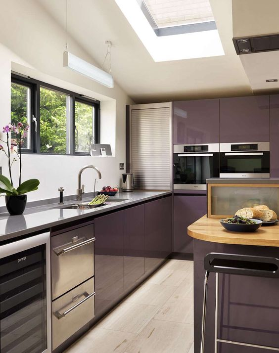 a purple kitchen with grey stone cabinets, potted plants and a window for more light is cool and chic