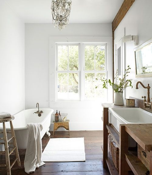 a refined bathroom with a stained wooden floor, a wooden console and some beams, a chic chandelier and some greenery