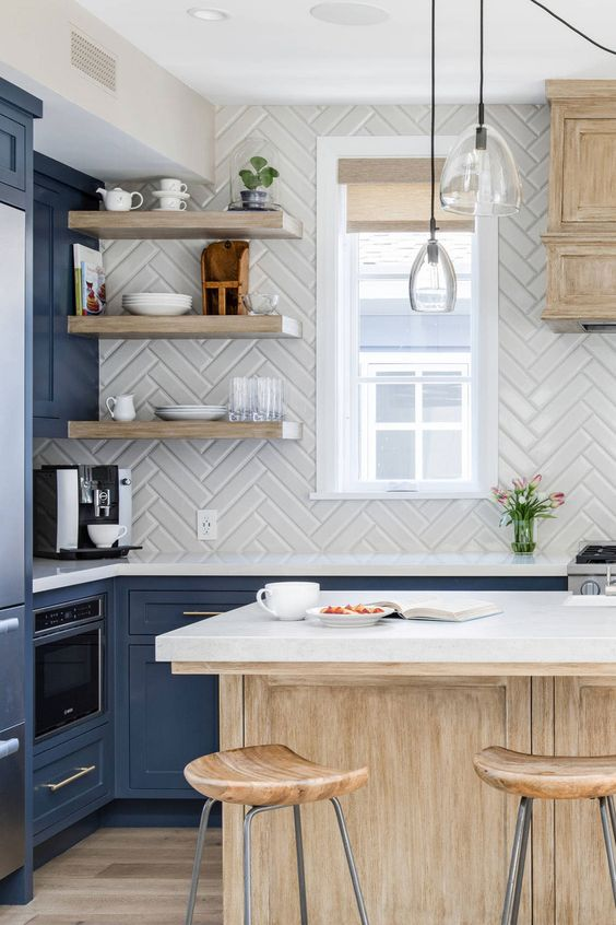a refined blue kitchen with a stained kitchen island and white countertops, a white herringbone backsplash and floating shelves