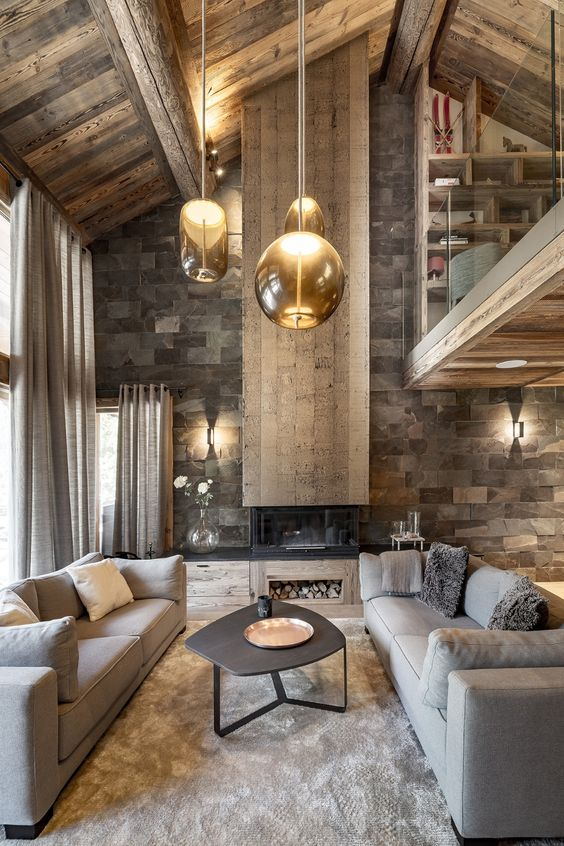 a refined chalet living room with a stone wall, a fireplace, a wooden ceiling, grey sofas and hanging glass lamps