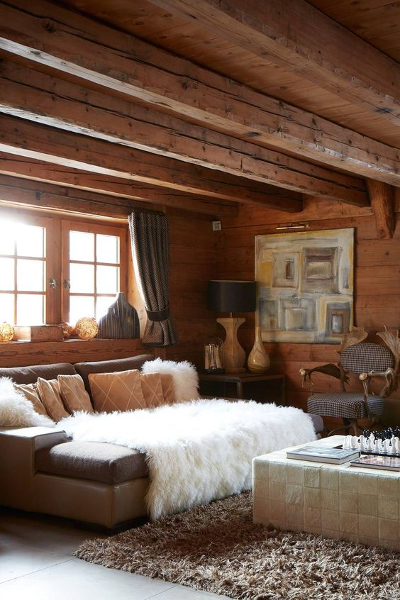 a refined chalet living room with walls, a ceiling and a floor of wood, neutral furniture and vintage lamps