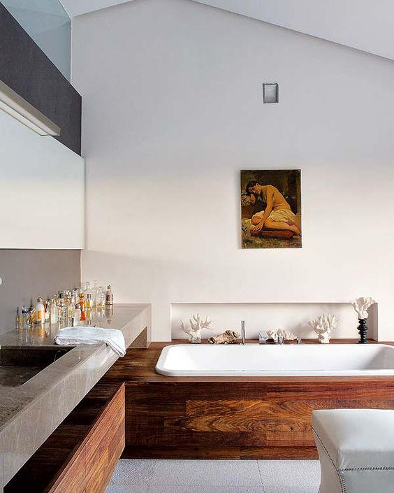 a refined contemporary bathroom with a bathtub in a slab of wood and a woode drawer under the concrete vanity
