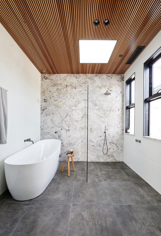 a refined contemporary bathroom with a wood clad ceiling, a stone wall and a stone tile floor is chic