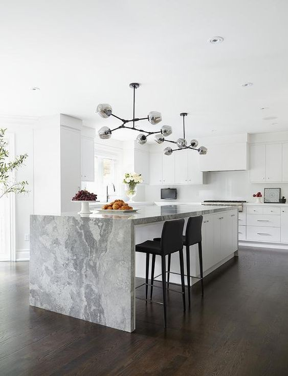 a refined contemporary kitchen in white with a large kitchen island and a grey stone waterfall countertop for more elegance
