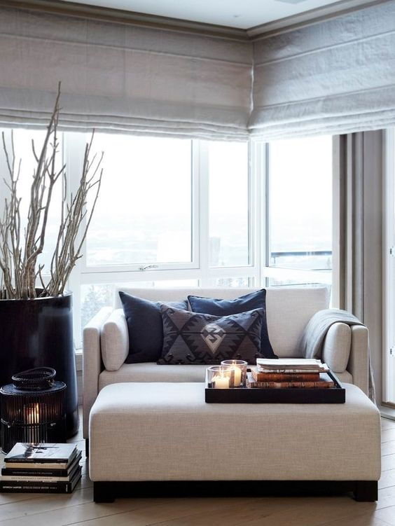 a refined contemporary living room with a loveseat and a matching ottoman, neutral shades and a branch arrangement in a vase
