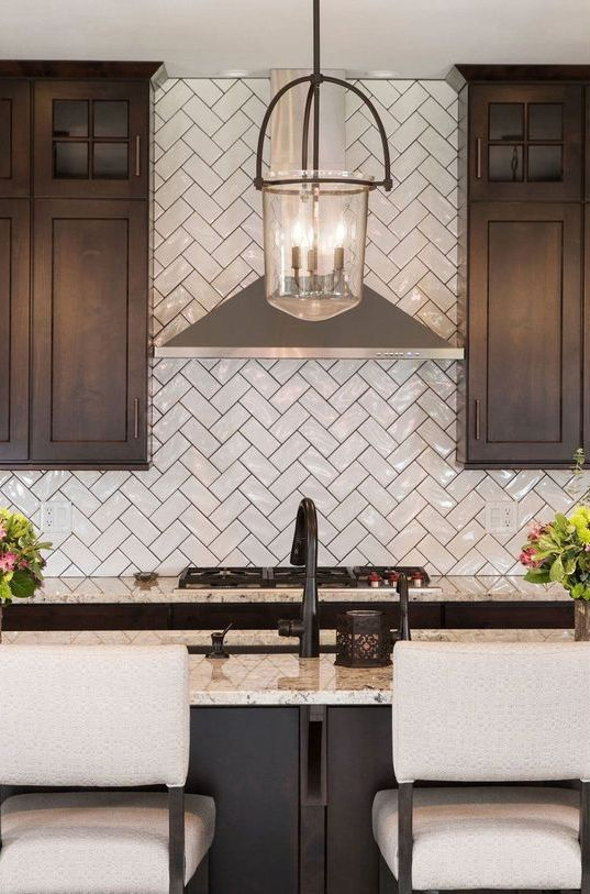 a refined dark kitchen with a glossy white herringbone backsplash and neutral quartz countertops plus upholstered stools