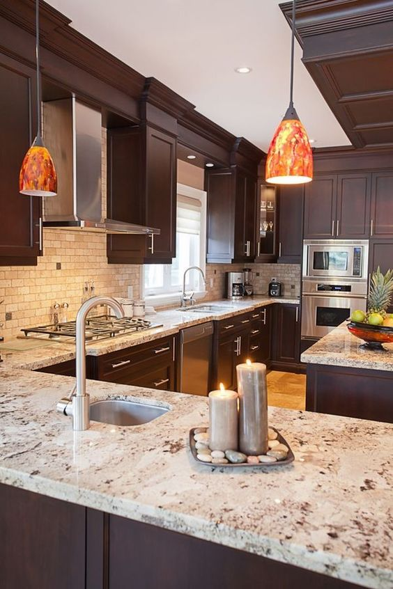 a refined dark kitchen with a tan tile backsplash and beautiful granite coutnertops that make the cbainetry stand out even more