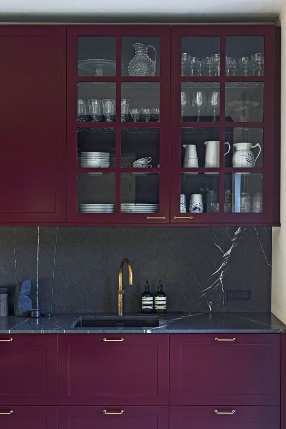 a refined deep purple kitchen with a black marble backsplash and countertops plus gold touches for an exquisite feel
