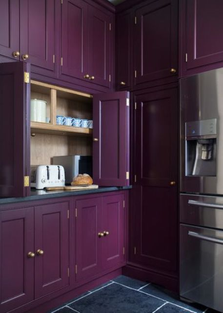 a refined deep purple kitchen with black countertops and niches hidden with folding doors is a very stylish idea