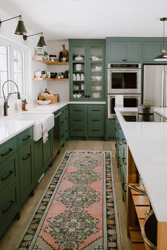 a refined green farmhouse kitchen with white quartz cabinets, black fixtures and handles, black sconces and open shelves in the corner