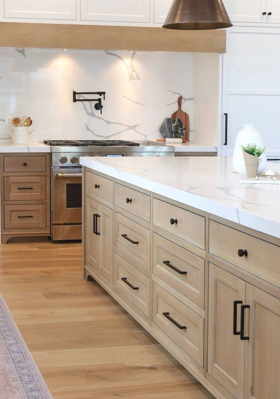 a refined modern farmhouse kitchen with stained cabinetry, white quartz countertops and a backsplash and black fixtures for a modern feel