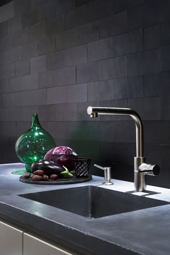 a refined modern kitchen with a concrete countertop and matte black tiles on the backsplash is a stylish and bold space