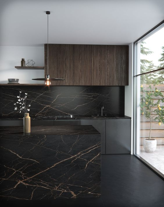a refined moody kitchen in black with a dark stained upper cabinet, a black marble backsplash, countertops and a kitchen island