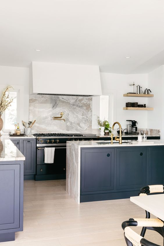 a refined navy kitchen with grey stone countertops including a waterfall one and a backsplash is very stylish