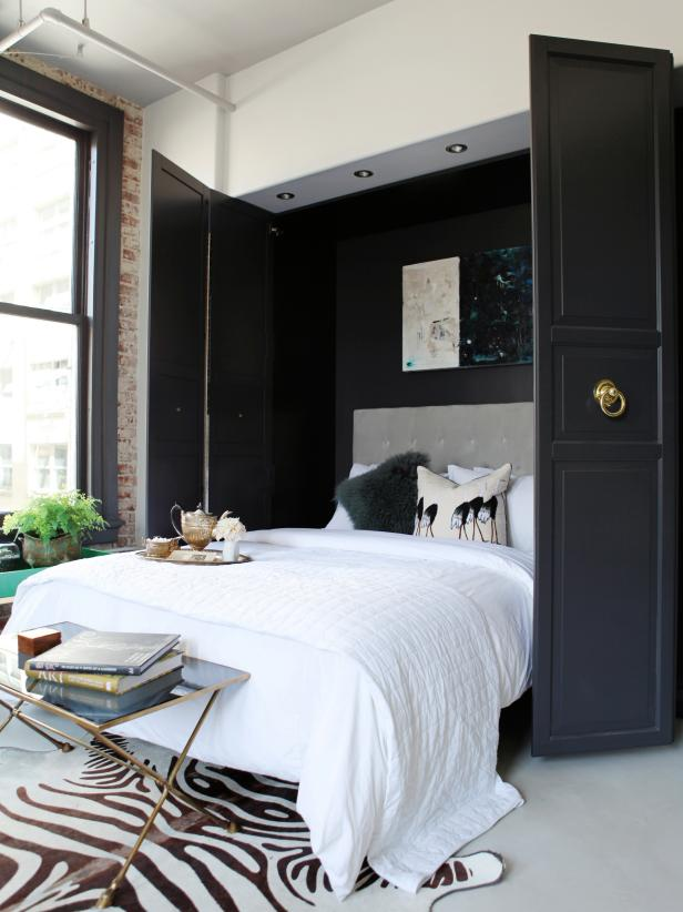 a refined space with a hidden Murphy bed with refined black doors and gold ring pulls plus touches of gold