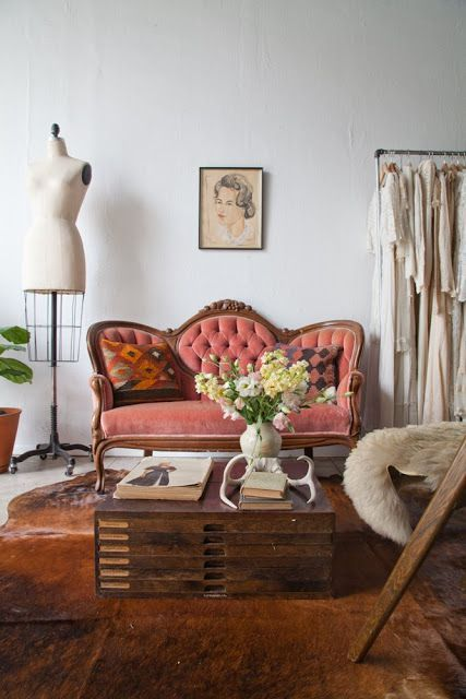 a refined vintage room with a peachy loveseat, a stacked table and an animal skin and neutral outfits