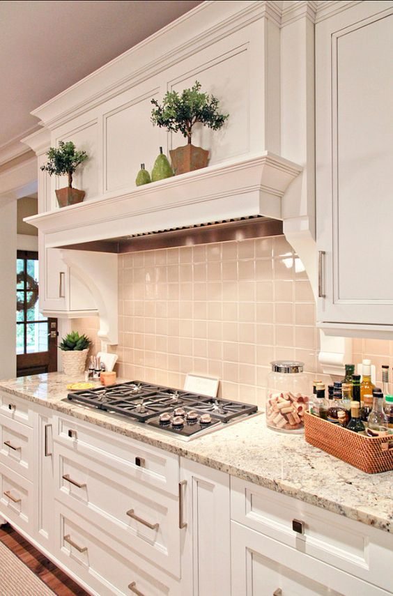 a refined white farmhouse kitchen with a grey tile backsplash and grey granite countertops plus built-in lights