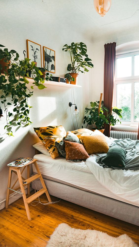 a relaxed boho bedroom in neutrals, with colorful textiles, potted greenery and climbing plants is very cozy