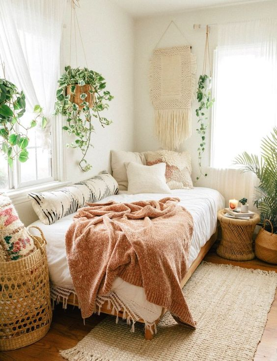 a relaxed boho bedroom in neutrals, with statement potted plants, some climbing ones and a macrame hanging on the wall