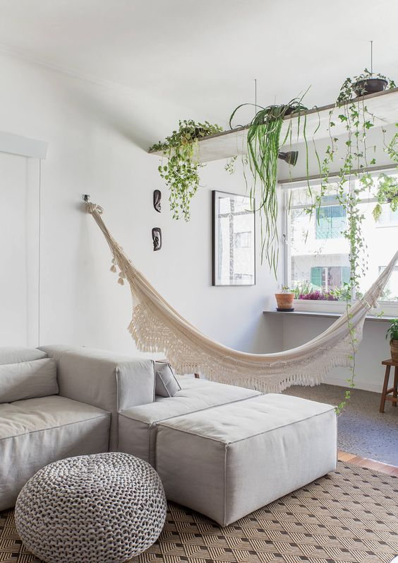 a relaxed neutral modern living room with an open shelf with climbing plants and a hammock feels very relaxed