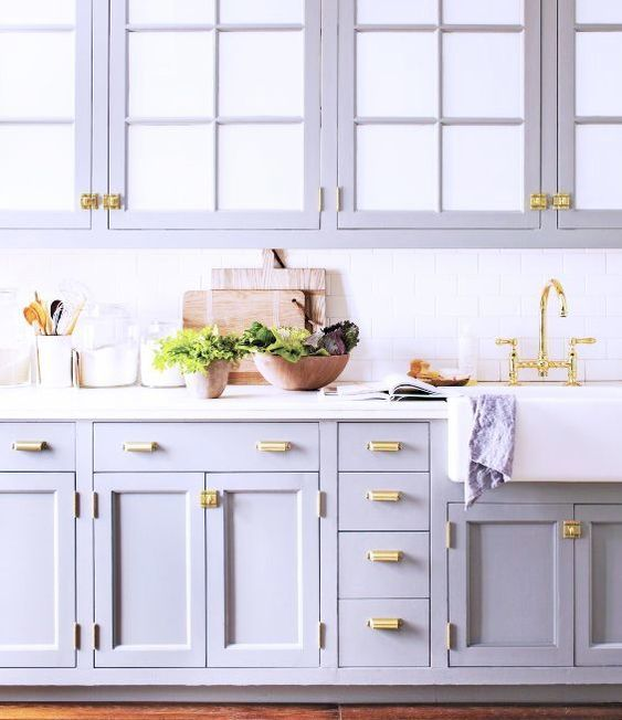 a romantic lilac kitchen with a white subway tile backsplash and a white countertop plus gold touches