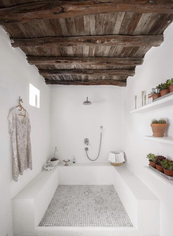 a rustic bathroom with a reclaimed wood ceiling with beams, white stone and tiles is a very cool space