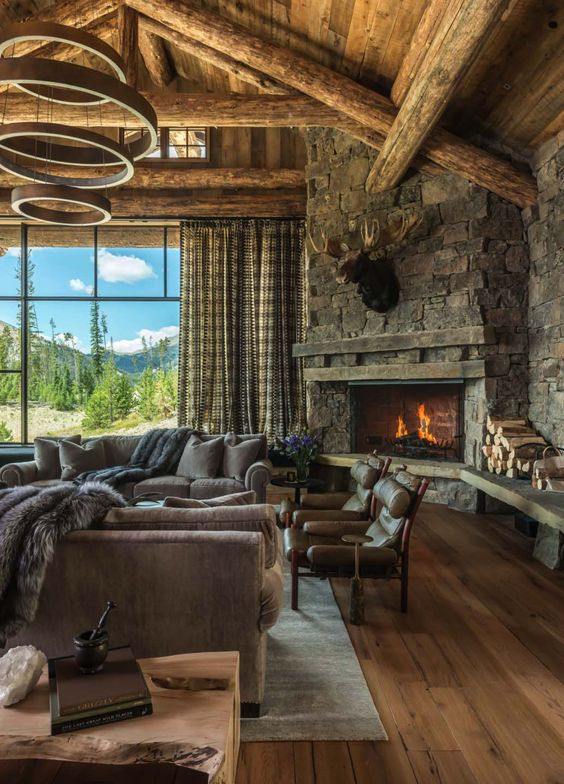 a rustic mountain living room with a wooden ceiling with beams, a stone clad fireplace and cozy furniture plus a catchy chandelier