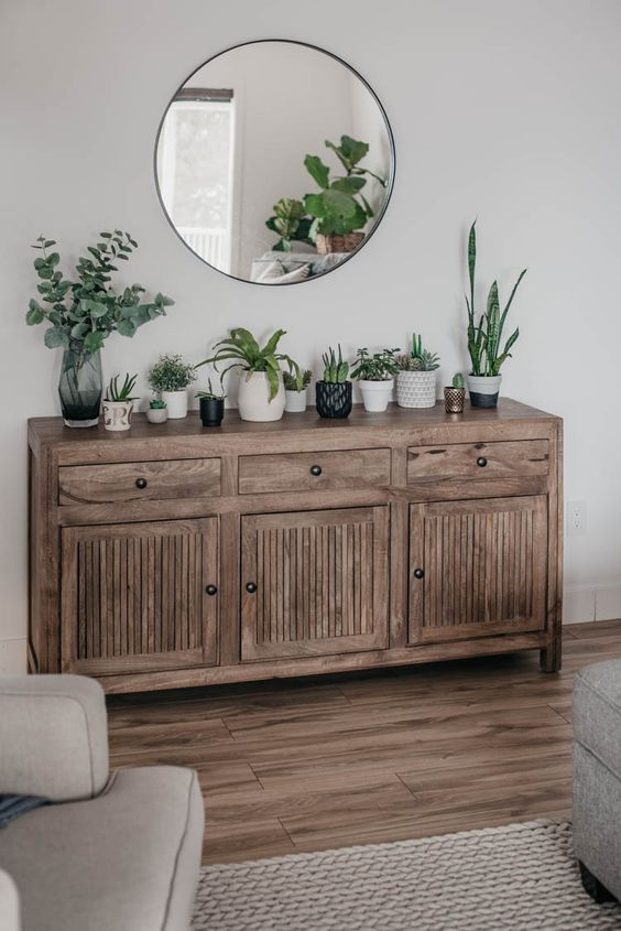 a rustic wooden console with lots of potted plants and greenery is a pretty idea to bring a spring feel to the space