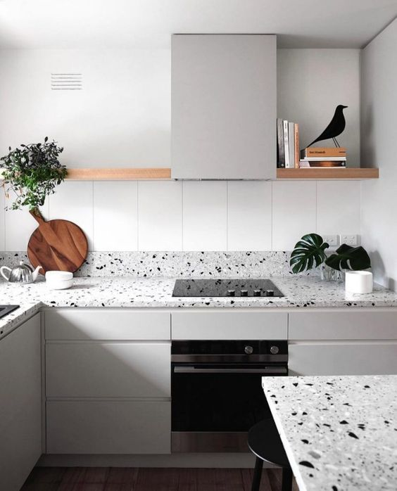 a serene Nordic kitchen with light grey cabinets and matching grey terrazzo countertops and a long open shelf instead of uppers