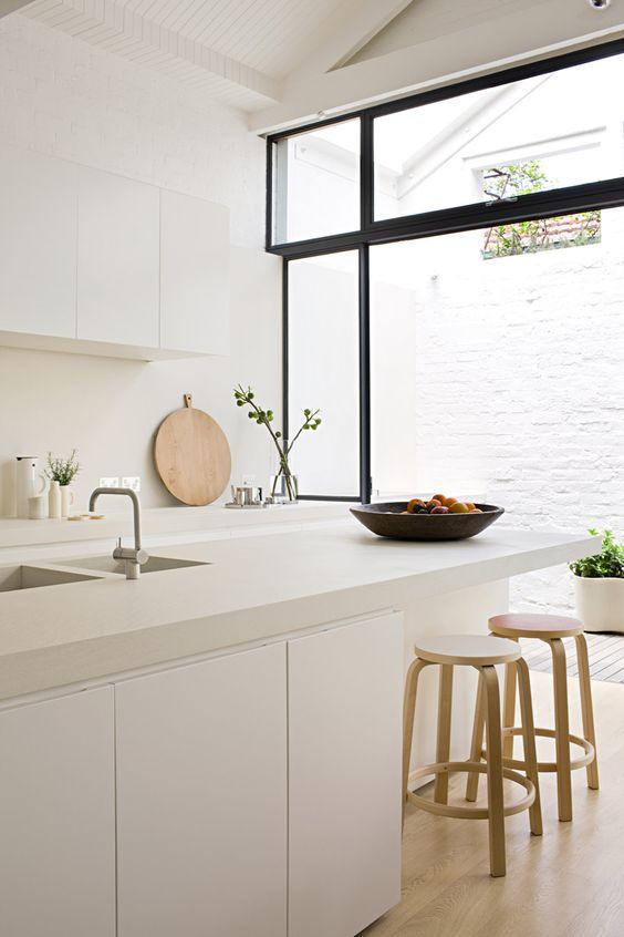 a serene white kitchen with sleek cabinets, a white tile backsplash and white concrete countertops is amazing