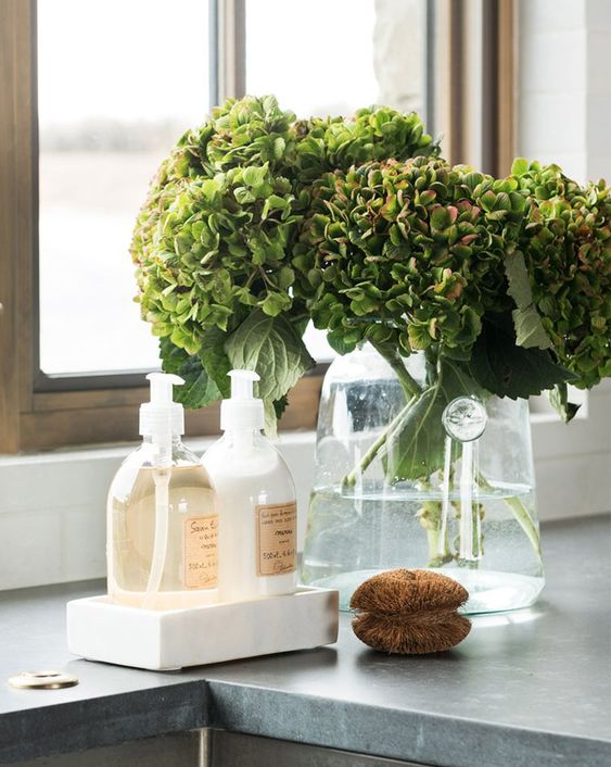 a sheer glass vase with green hydrangeas is a cool and simple spring decoration that can be used in any space