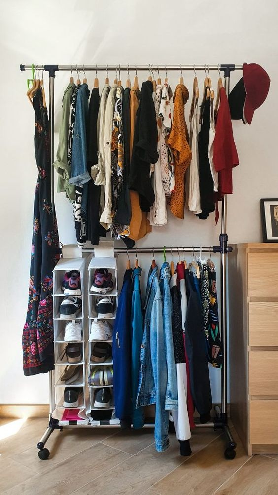 a simple makeshift closet with a double hanging shoe shelf and a dresser for small things next to it is a cool idea