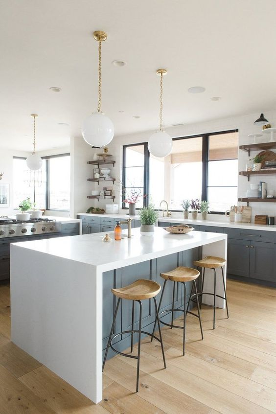 a slate grey kitchen with white coutnertops and a waterfall countertop on the kitchen island plus wooden stools and pendant lamps