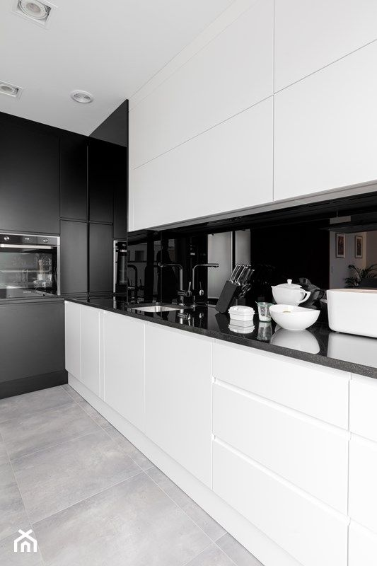 a sleek black and white kitchen with glossy black coutnertops and a black glass backsplash plus black fixtures just wows