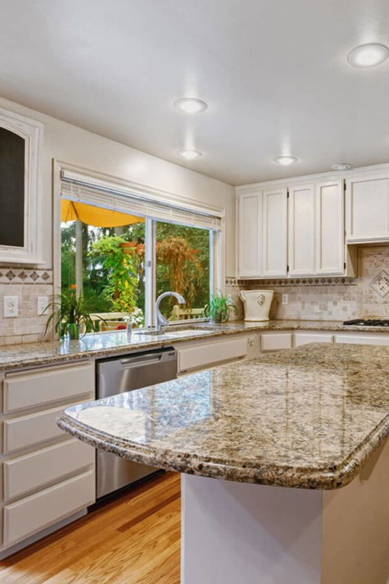 a sleek white kitchen with a tan tile backsplash and grey granite countertops is a stylish space in mid-century modern style