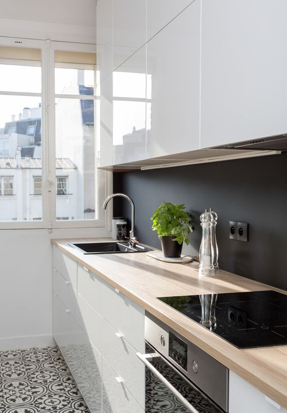 a sleek white kitchen with butcherblock countertops and a chalkboard backsplash to create a contrast here