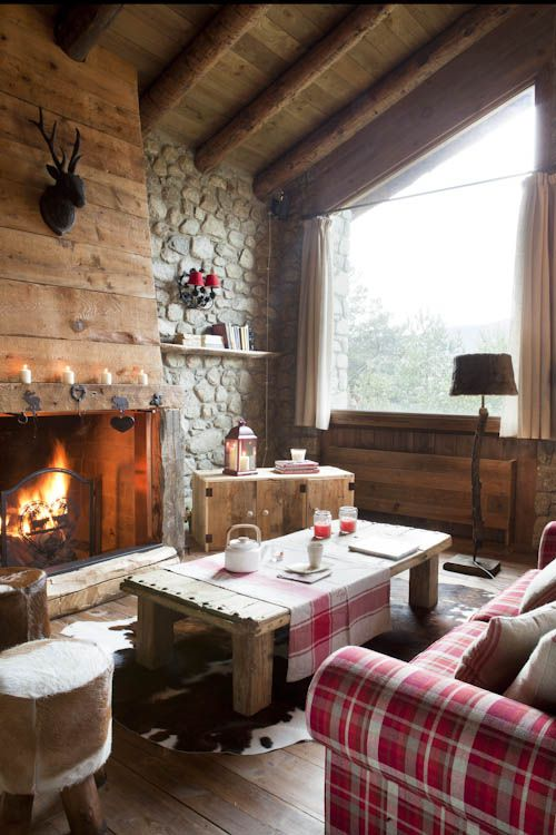 a small and cozy chalet living room with stone walls, a wood clad fireplace, wooden furniture and some upholstered units