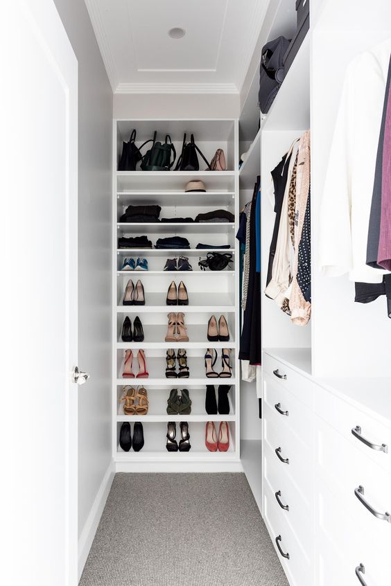 a small and narrow white walk-in closet with holders for clothes, open shelves for shoes, drawers for smaller stuff is cool and organized