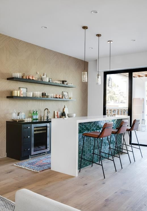 a small black kitchen with open shelves, a creative kitchen island with a waterfall countertop and green tiles