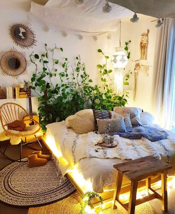 a small boho bedroom with a lit up pallet bed, wooden and rattan chairs, mirrors, indoor vines climbing up and a pendant lamp