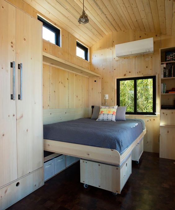 a small cabin with a large storage unit and a Murphy bed placed on ottomans, which is a clever solution