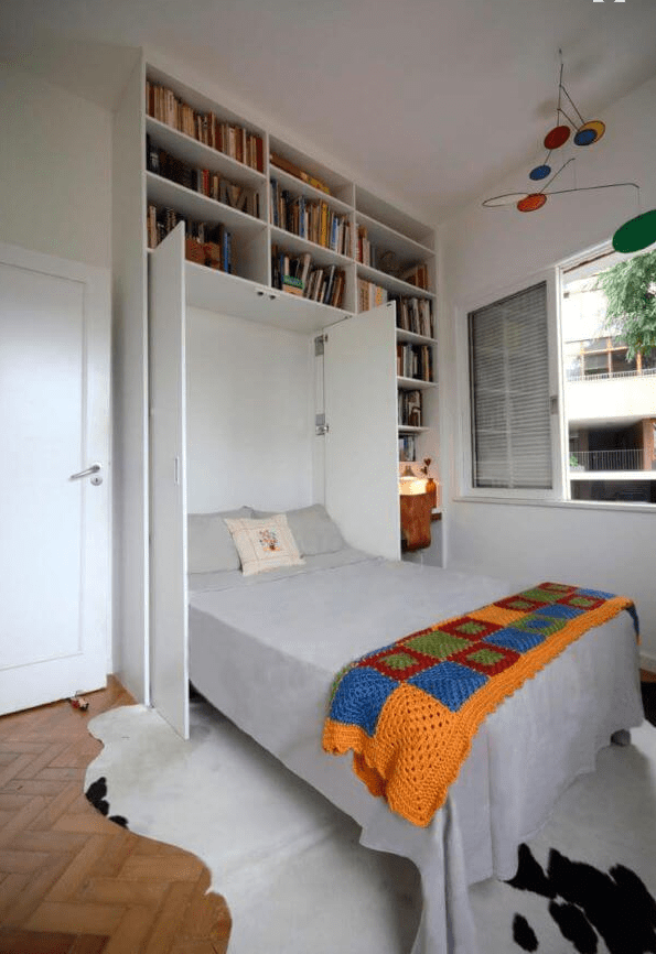 a small colorful room with open bookshelves and a Murphy bed hidden by the doors is a cool idea