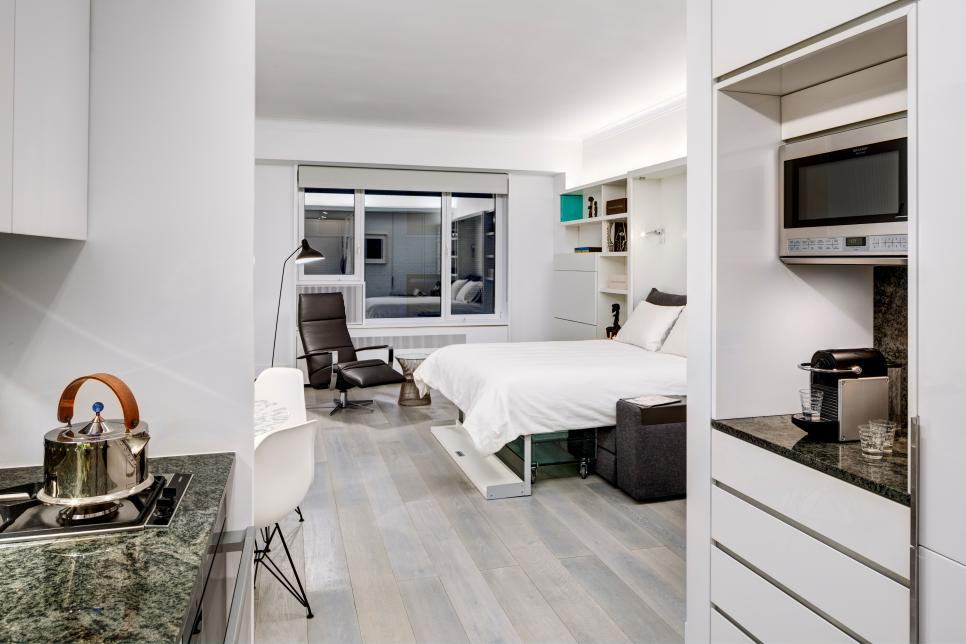 a small minimalist apartment with a large storage unit that takes a whole wall and contains a Murphy bed that saves space