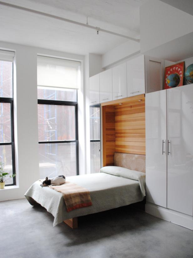 a small minimalist bedroom with a large storage unit, a Murphy bed and much natural light is a cool idea