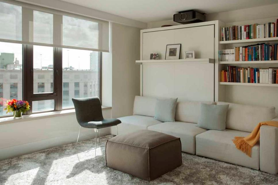 a small neutral living room with neutral upholstered sofa, a Murphy bed and comfy chairs and an ottoman