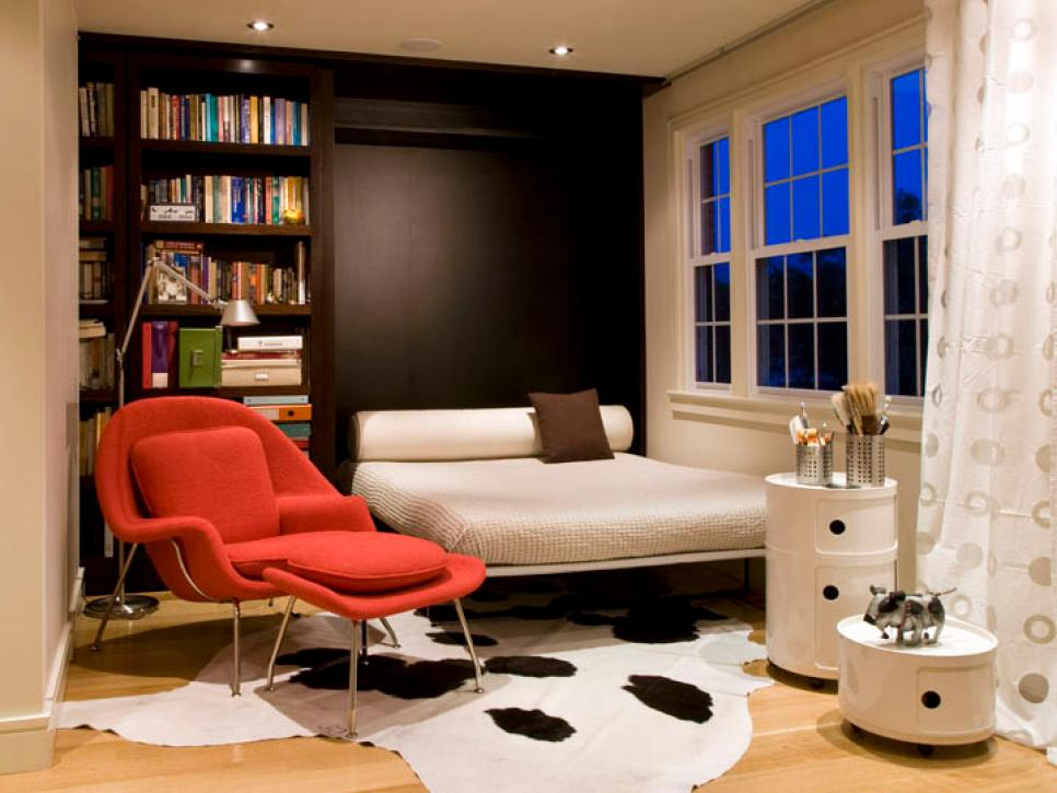 a small quirky room with a dark storage unit, a Murphy bed, a pretty red chair and cool side tables