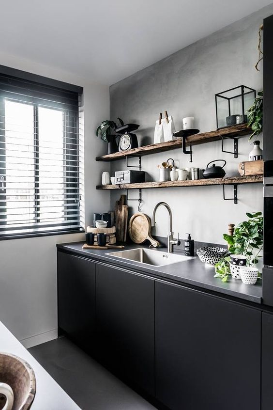 a small sleek black kitchen with a concrete countertop, open shelves on the wall and black touches for drama