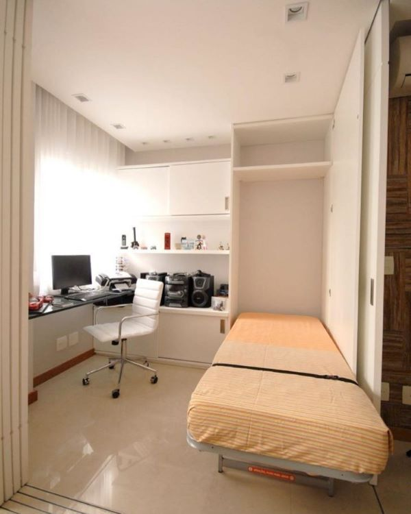 a small student room with a windowsill desk, storage units and a Murphy bed in the wardrobe